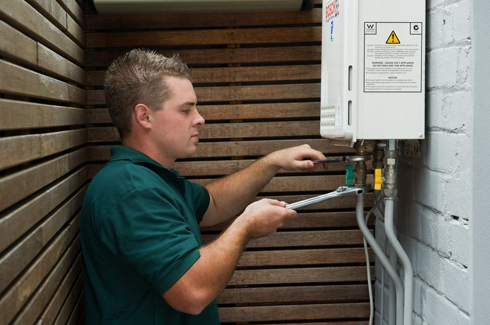 Gas fitter adjust a gas heater at a residential home