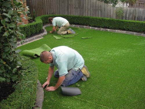 two men laying artificial turf in a garden