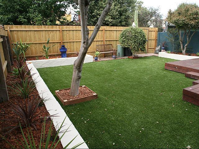 Artificial lawn in a backyard with raised flower beds and decking